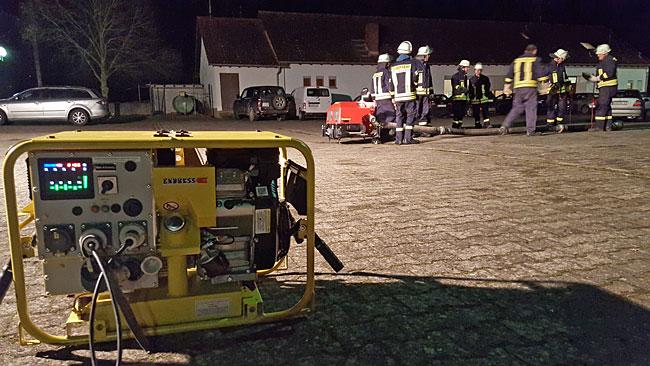 Nächtliche Feuerwehrübung unter Scheinwerfern auf dem Parkplatz der Dorfgemeinschaftshalle