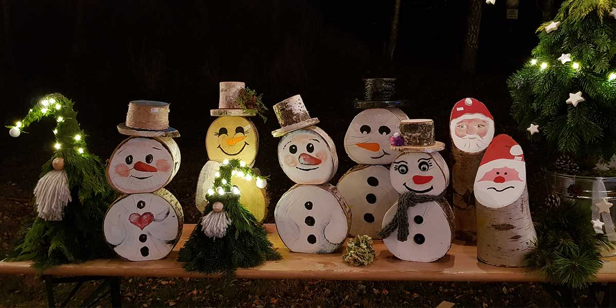 Liebevoll bemalte Schneemänner aus Baumscheiben