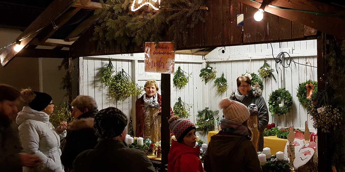 Buden mit Mistelzweigen, Adventsgestecken und Holzfiguren